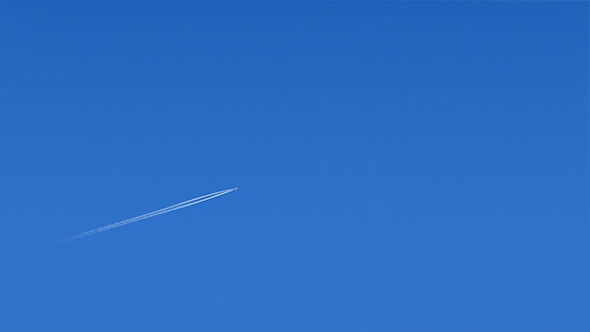 Plane Flies Across Blue Sky
