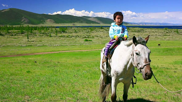 Young Baby Girl On Horseback In Steppe