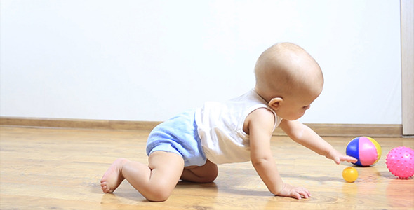 Little Baby Crawling on Floor to a Toy