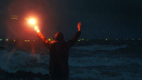Man Waving with Signal Road Flare for Help