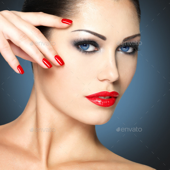 Beautiful woman with red nails and blue eyes