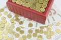 Gold coins and red treasure box on bills
