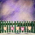 snow-covered wooden fence with hanging on it with paper hearts - PhotoDune Item for Sale