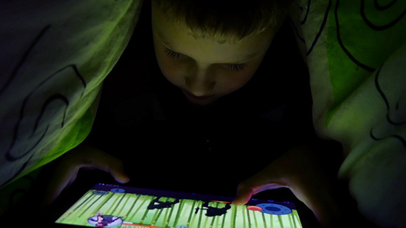 Young Boy Uses A Digital Tablet Under The Covers