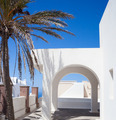 Traditional Greek architecture with white arch on blue sky. - PhotoDune Item for Sale