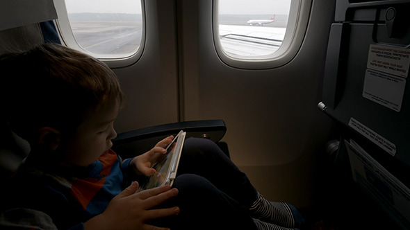 VideoHive Boy Using Tablet Pc In Plane Going To Take Off 10119296