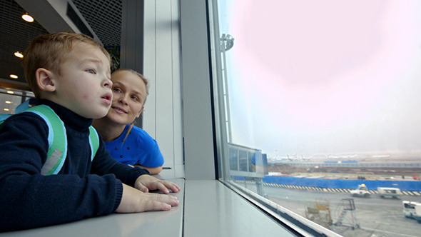 VideoHive Mother And Son Looking Out The Window At Airport 10119323