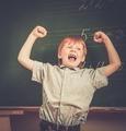 Little funny redhead schoolboy near blackboard
