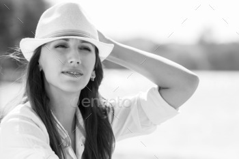 Caucasian girl in hat at summer midday near the river or lake.