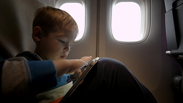 VideoHive Little Boy Playing On Touch Pad In The Plane 10133445