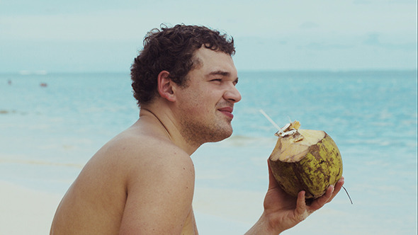 VideoHive Man On The Beach Drinking From Coconut 10133631