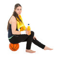 Pretty woman in sports wear sitting on basketball drinking juice - PhotoDune Item for Sale