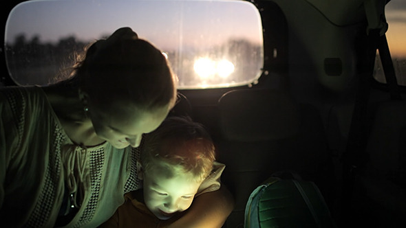 Mother And Son Using Touch Pad In Car At Night