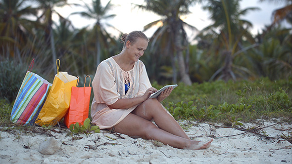 VideoHive Woman After Shopping Using Tablet Pc On The Beach 10143657