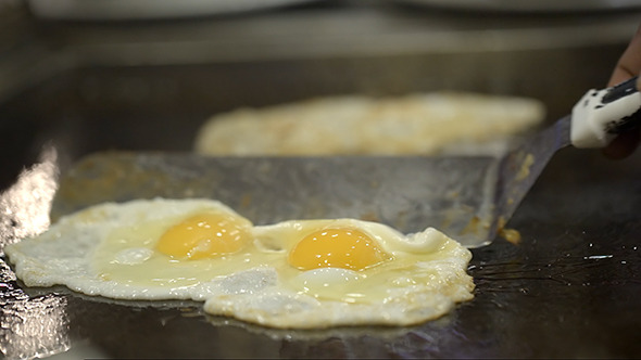 Two Portions Of Fried Eggs Cooked On The Stove