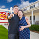 Happy Hispanic Couple In Front of New Home And Sold Real Estate Sign Showing Off Their House Keys. - PhotoDune Item for Sale