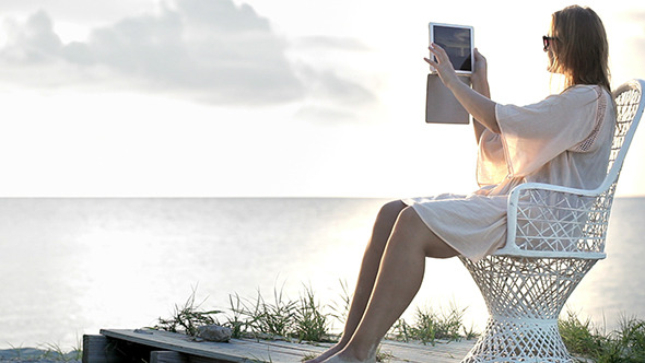 VideoHive Woman Near The Sea Making Photos Using Pad 10147968