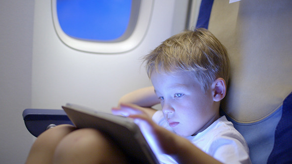 VideoHive Bored Or Tired Boy In Plane Using Tablet Computer 10150133