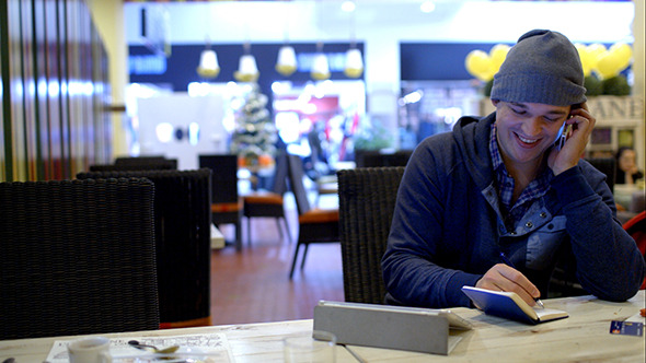 VideoHive Young Man In Cafe Speaks Phone And Writes Down 10151109