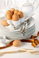 Eggs in white egg cups on a pile of plates with ribbons - PhotoDune Item for Sale
