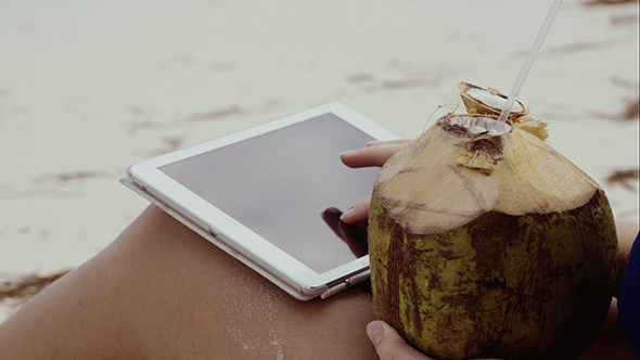 Woman Using Touch Pad And Having Coconut Drink