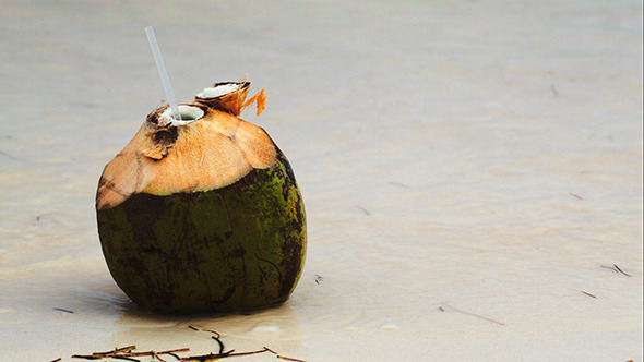 Coconut By The Sea With Female Hand Putting Straw