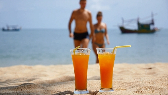 Couple Resting on the Beach with Cocktails
