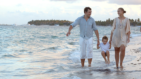 Parents And Their Child Walking Along The Beach