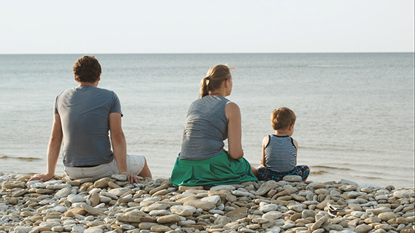 Family Of Three Sitting On Pebble Beach By Water