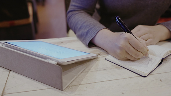 Woman Taking Notes In Notebook Touch Pad Nearby