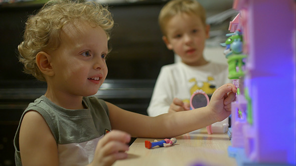 Little Boys Playing With Toy House At Home
