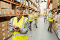 Smiling male manager using handheld in a large warehouse - PhotoDune Item for Sale
