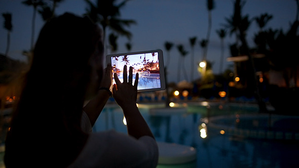 Woman Using Pad To Take Photos On Tropical Resort