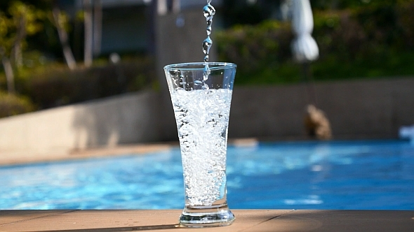 Pouring Water in Glass near Pool