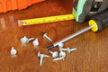 Measure tape and a screwdriver with screws on the wooden table - PhotoDune Item for Sale