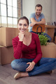 Smiling woman sitting in front of packing cases - PhotoDune Item for Sale