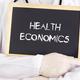 Doctor shows information on blackboard: health economics - PhotoDune Item for Sale