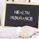Doctor shows information on blackboard: health insurance - PhotoDune Item for Sale
