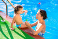 Baby girl blowing soap ballons with mother in pool - PhotoDune Item for Sale