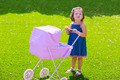Toddler kid girl playing with baby cart in green turf - PhotoDune Item for Sale