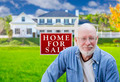 Senior Adult Man in Front of Home For Sale Real Estate Sign and Beautiful House. - PhotoDune Item for Sale
