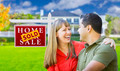 Happy Mixed Race Couple in Front of Sold Home For Sale Real Estate Sign and House. - PhotoDune Item for Sale