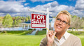Attractive Young Adult Woman with Pencil in Front of For Sale Real Estate Sign and House. - PhotoDune Item for Sale