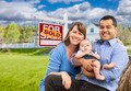 Happy Mixed Race Young Family in Front of Sold Home For Sale Real Estate Sign and House. - PhotoDune Item for Sale