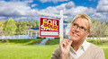 Attractive Young Adult Woman with Pencil in Front of Sold For Sale Real Estate Sign and House. - PhotoDune Item for Sale