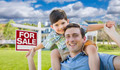 Father and Son Celebrating with a Piggyback in Front Their House and For Sale Sign - PhotoDune Item for Sale