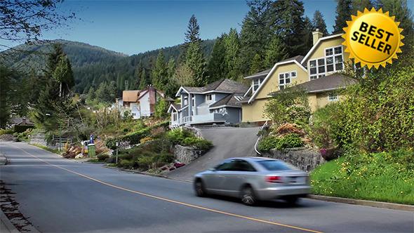 Car Drives Through Pretty Suburbia