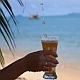 Female Hand with a Glass of Ice Tea on the Beach - VideoHive Item for Sale