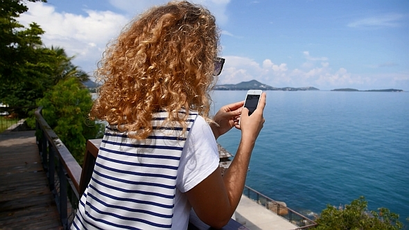 Woman with Smartpone against Sea