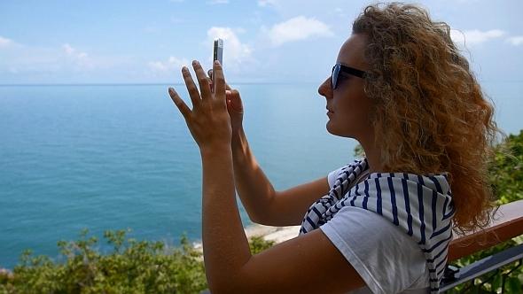 Woman Taking Photo of Sea